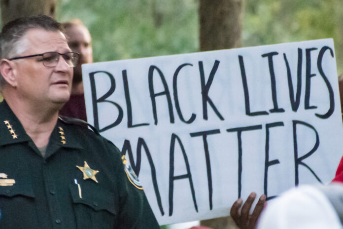 Sheriff Ivey in front of BLM sign.